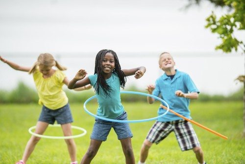 Kids playing outside with hula hoops.