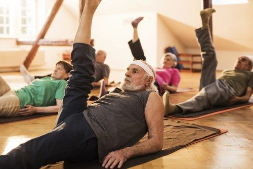 Group of senior men and women lying in a health club and doing Pilates exercises.